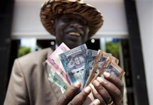 165002-a-man-from-south-sudan-displays-new-currency-notes-outside-the-central
